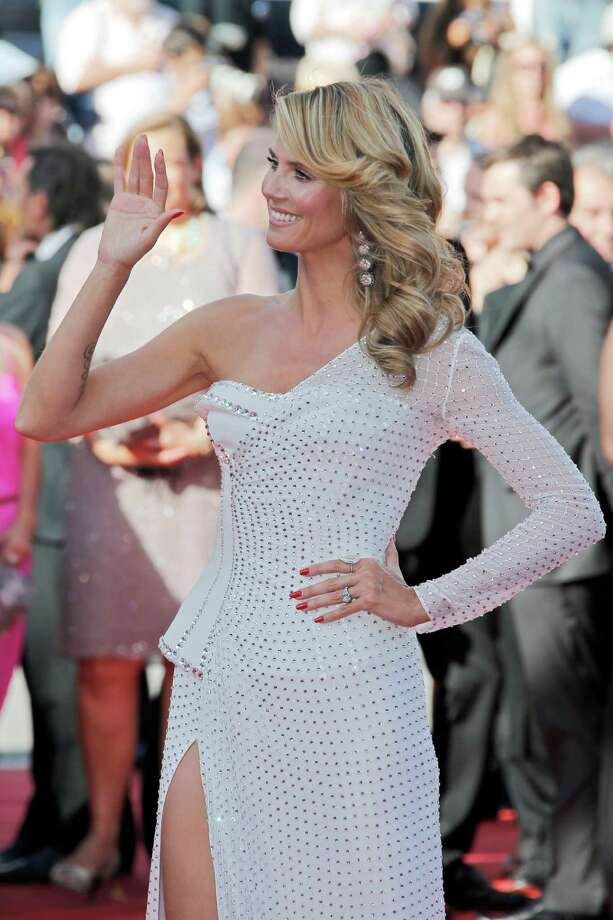 Model Heidi Klum gestures as she poses for photographers while she arrives for the screening of Nebraska at the 66th international film festival, in Cannes, southern France, Thursday, May 23, 2013. Photo: AP