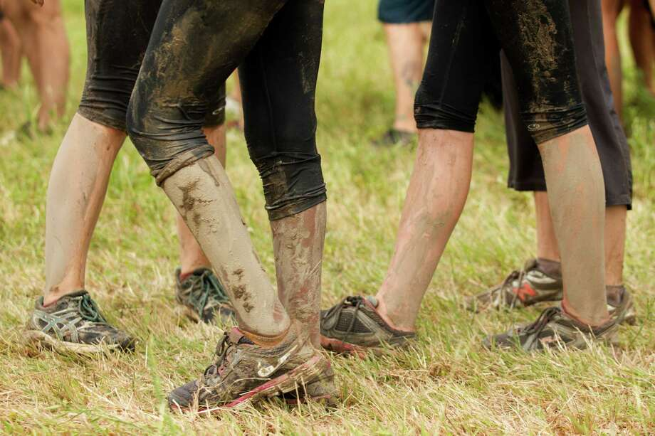 Mud cakes the legs of racers during The Original Mud Run at Sam Houston Race Park Saturday, May 25, 2013, in Houston. Participants raced through 5K and 10K courses, over, under and through more than 20 muddy obstacles to benefit feedOne. Photo: Brett Coomer, Houston Chronicle / © 2013 Houston Chronicle
