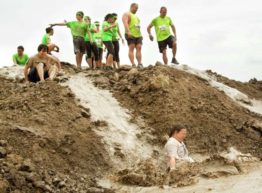 Racers in The Original Mud Run splash down in a mud pit as they race toward the finish line at Sam Houston Race Park Saturday, May 25, 2013, in Houston. Participants raced through 5K and 10K courses, over, under and through more than 20 muddy obstacles to benefit feedOne. Photo: Brett Coomer, Houston Chronicle / © 2013 Houston Chronicle