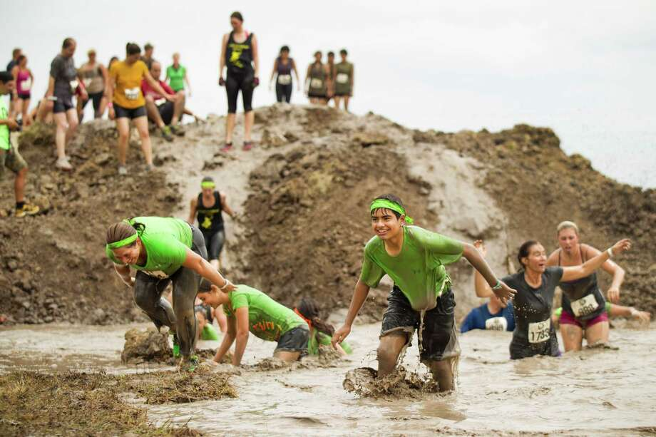 Racers in The Original Mud Run make their way through a mud pit as they race toward the finish line at Sam Houston Race Park Saturday, May 25, 2013, in Houston. Participants raced through 5K and 10K courses, over, under and through more than 20 muddy obstacles to benefit feedOne. Photo: Brett Coomer, Houston Chronicle / © 2013 Houston Chronicle