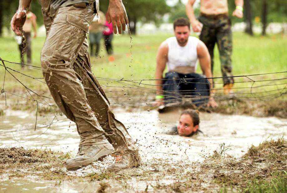 Racers splash through a mud pit during The Original Mud Run at Sam Houston Race Park Saturday, May 25, 2013, in Houston. Participants raced through 5K and 10K courses, over, under and through more than 20 muddy obstacles to benefit feedOne. Photo: Brett Coomer, Houston Chronicle / © 2013 Houston Chronicle