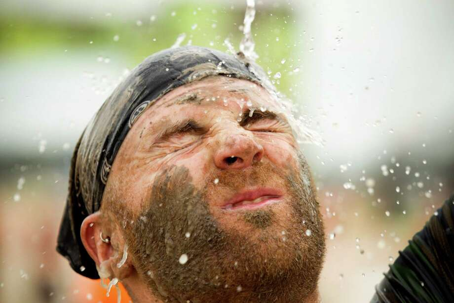 Joshua Avalo splashes fresh water on his face after he finished The Original Mud Run at Sam Houston Race Park Saturday, May 25, 2013, in Houston. Participants raced through 5K and 10K courses, over, under and through more than 20 muddy obstacles to benefit feedOne. Photo: Brett Coomer, Houston Chronicle / © 2013 Houston Chronicle