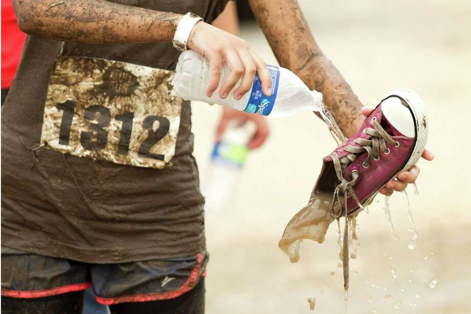 A racers pours fresh water on her shoe at the end of The Original Mud Run at Sam Houston Race Park Saturday, May 25, 2013, in Houston. Participants raced through 5K and 10K courses, over, under and through more than 20 muddy obstacles to benefit feedOne. Photo: Brett Coomer, Houston Chronicle / © 2013 Houston Chronicle