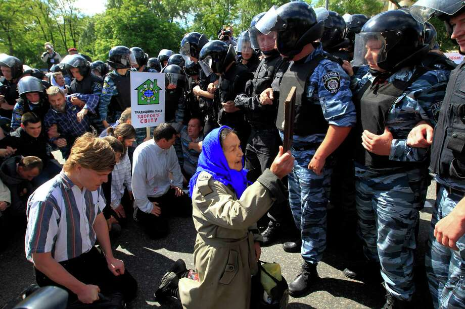 Riot police stop Orthodox protesters who are trying to stop Ukraine's first gay pride demonstration in Kiev, Ukraine, Saturday, May 25, 2013. About a hundred gay and lesbian Ukrainians and those from other countries took part in the gay pride rally, protected by hundreds of riot police. Antipathy toward homosexuals remains strong in Ukraine. The poster reads: ' The traditional family is health of the world '. Photo: AP