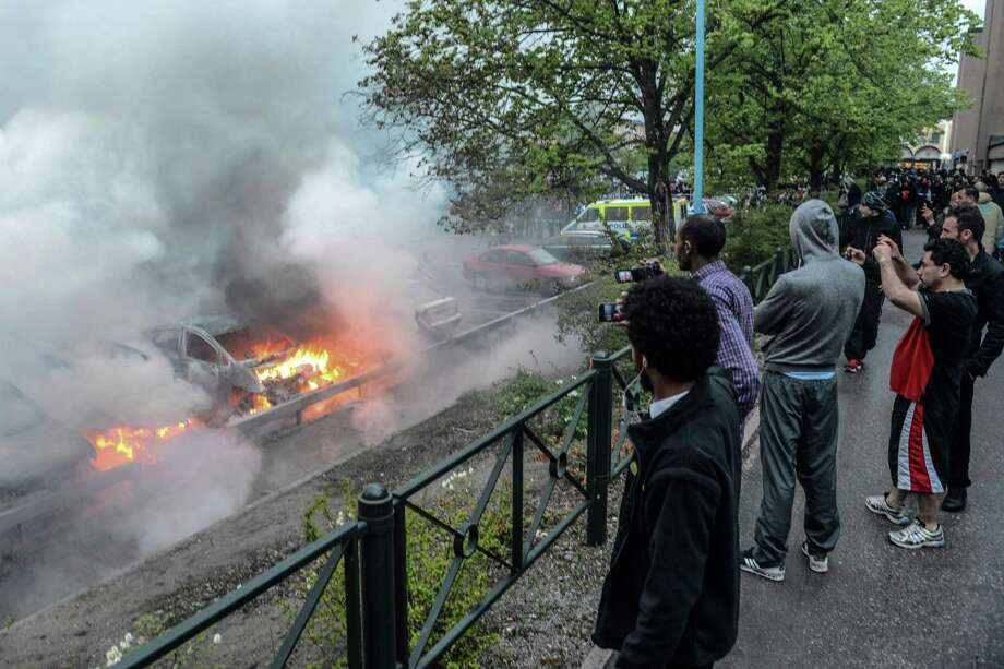 Bystanders take photos of a row of burning cars in the Stockholm suburb of Rinkeby after youths rioted in several different suburbs around Stockholm for a fourth consecutive night, late Thursday May 23, 2013. Youths in immigrant-heavy Stockholm suburbs torched cars and threw rocks at police in riots believed to be linked to a deadly police shooting of a local resident in the suburb of Husby. (AP Photo/Scanpix, Fredrik Sandberg) Photo: AP