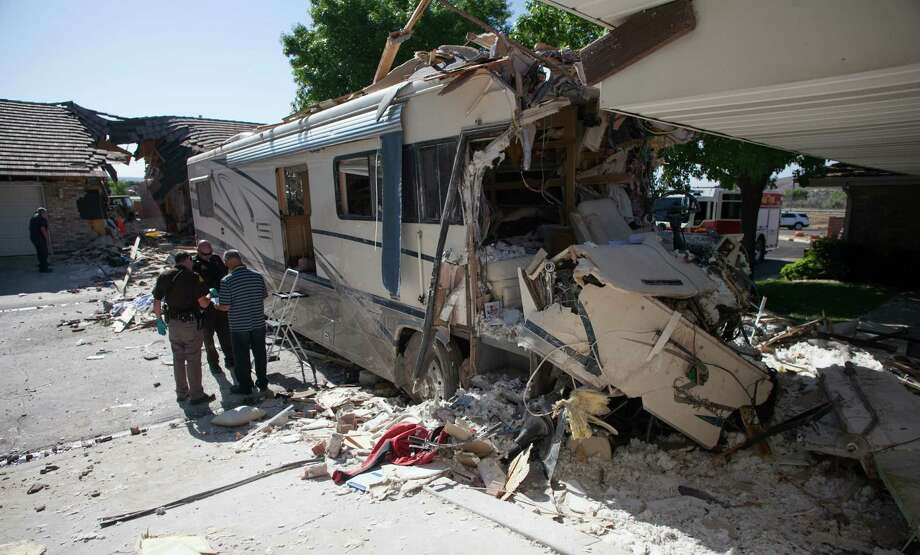 Police investigate after a motorhome crashed into several townhomes, Friday, May 24, 2013 in St. George, Utah. A Provo couple on a family recreational vehicle trip was killed when their motorhome crashed into several St. George townhomes, authorities said. (AP Photo/The Spectrum, Jud Burkett) Photo: AP