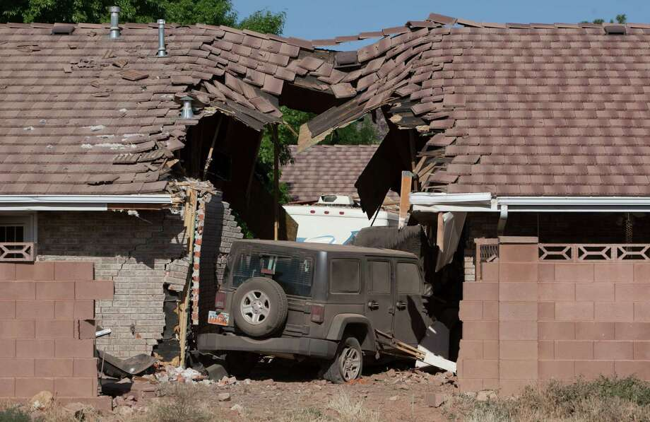A Jeep that was being towed behind an RV crashed into several townhomes, Friday, May 24, 2013 in St. George, Utah. A Provo couple on a family recreational vehicle trip was killed when their motorhome crashed into several St. George townhomes, authorities said. (AP Photo/The Spectrum, Jud Burkett) Photo: AP