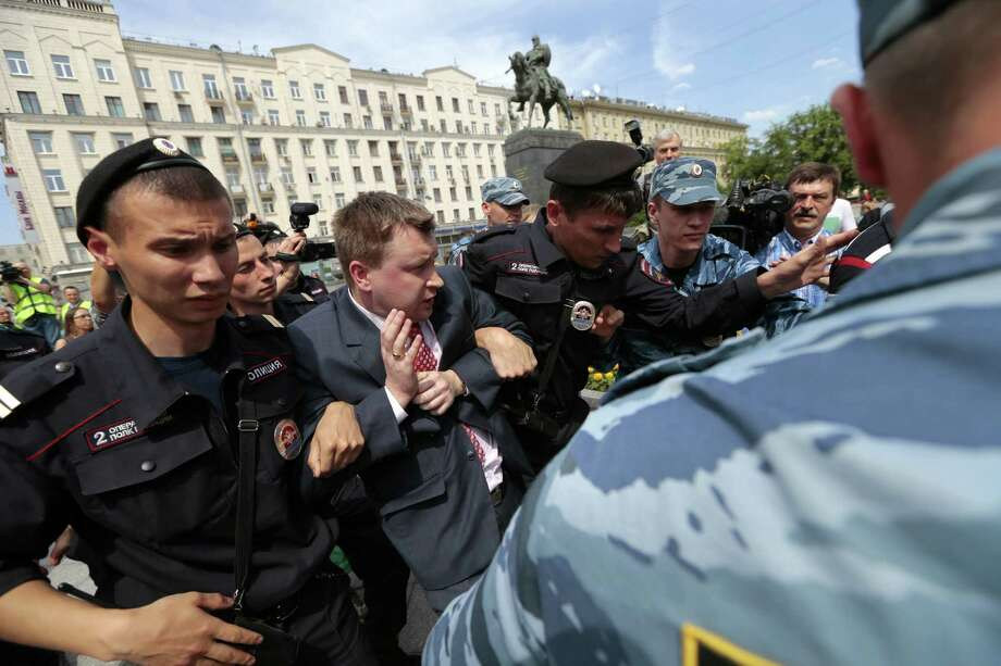 "Police detain Russia's leading gay rights campaigner Nikolai Alexeyev during an unsanctioned gay rally near the City Hall in Moscow, Saturday, May 25, 2013. The Kremlin initiated a bill banning ""propaganda of homosexuality"" and routinely banned gay rallies and parade.  In the background is a monument to Moscow's founder Yuri Dolgoruky. Photo: AP"