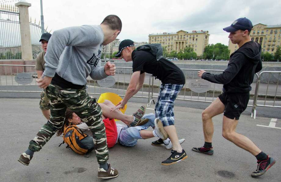 "Nationalist activists attack a gay rights campaigner at a park in Moscow, Saturday, May 25, 2013.  Gay-rights campaigners and their opponents clashed at an unsanctioned rally in the Russian capital on Saturday. The Kremlin initiated a bill banning ""propaganda of homosexuality"" and routinely banned gay rallies and parade. Photo: AP"