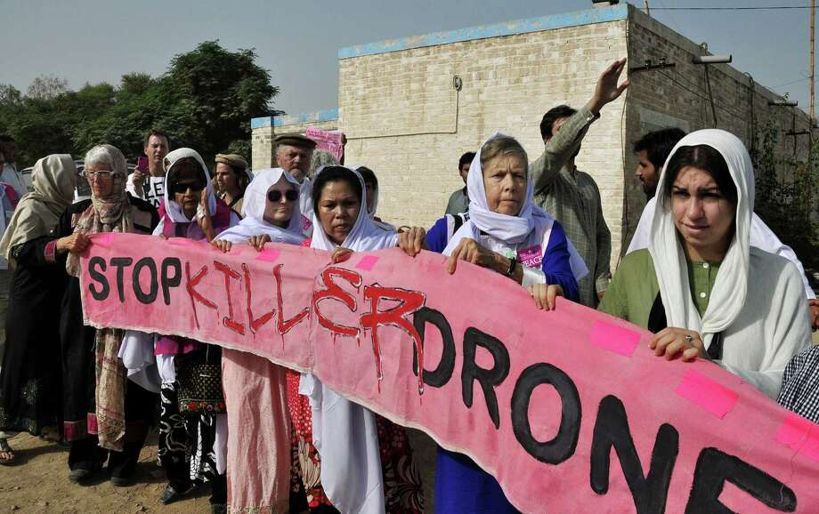 In this Sunday, Oct. 7, 2012 file photo, American citizens, hold a banner during a peace march organized by Pakistan's cricket star turned politician Imran Khan's party, not pictured, in Tank, Pakistan. President Barack Obama�s decision announced Thursday, May 23, 2013, to impose more restrictive rules governing U.S. drone strikes and his prediction that they will be used less could pave the way for better relations with key ally Pakistan as a new government takes power. Obama fell short of Pakistani demands to announce an end to the attacks altogether in a landmark speech, but his comments were seen as addressing some of the country's main concerns over the CIA program. Photo: AP
