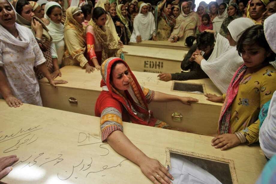 Pakistani women mourn the death of their relatives, who were killed in gas cylinder explosion on a minibus, in Gujrat, Pakistan, Saturday, May 25, 2013. Police say that a teacher was among more than a dozen people burned to death in eastern Pakistan when a minibus taking children to school suddenly caught fire. Photo: AP