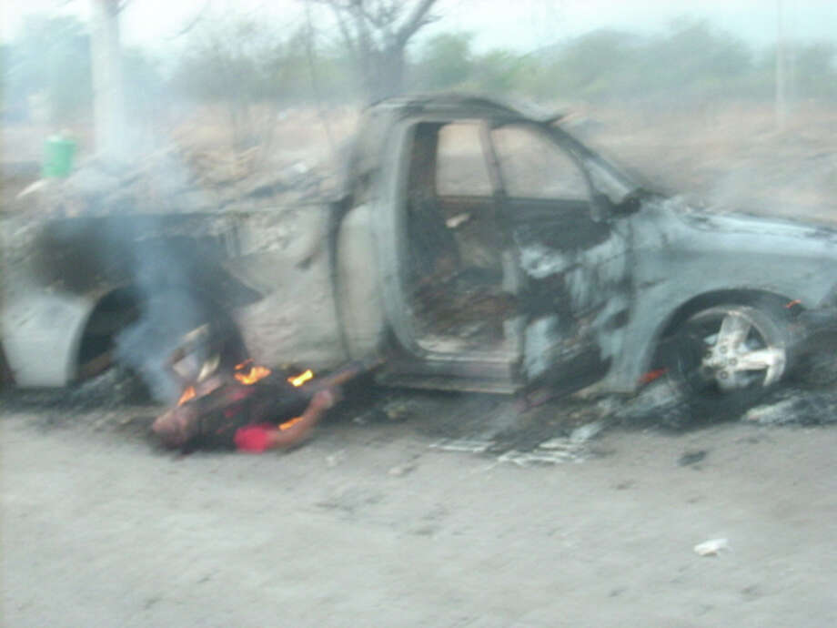 In this April 28, 2013 image obtained by the Associated Press from members of La Ruana Community Police, May 19, 2013, the burning body of a man lies next to the charred shell of a vehicle allegedly belonging to the Knights Templar drug gang, near La Ruana, Mexico. According to La Ruana Community Police, a post manned by them and the Mexican army opened fire on a convoy of the Knights Templar when they tried to enter the town. Dozens of Knights Templar members and four community policemen were killed in the gunfight. Photo: AP