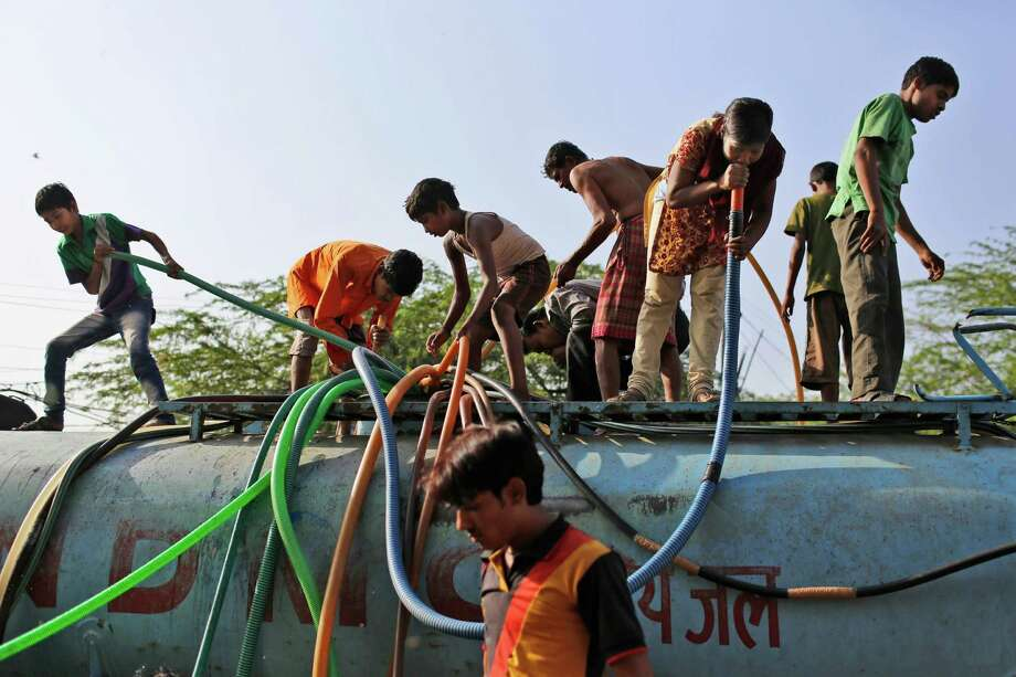 An Indian girl sucks on a hose to pull water as she stand on top of a government tanker delivering drinking water because of short supply in running water taps at a slum in New Delhi, India, Friday, May 24, 2013. Many areas of the Indian capital are facing acute water shortage, a repeated annual phenomenon during summer when taps go dry as demand rises. Photo: AP