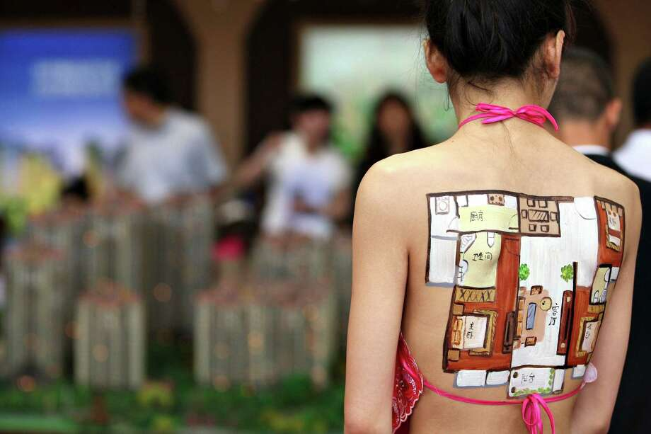 In this photo released by China's Xinhua News Agency, a model has her back painted with the floor plan of a house as a way to attract attention by customers during the 55th Housing Fair held in Nantong City, east China's Jiangsu Province, on Friday, May 24, 2013. The housing fair, featuring variety of publicizing methods, opened on Friday. (AP Photo/Xinhua, Cui Genyuan)  Photo: AP