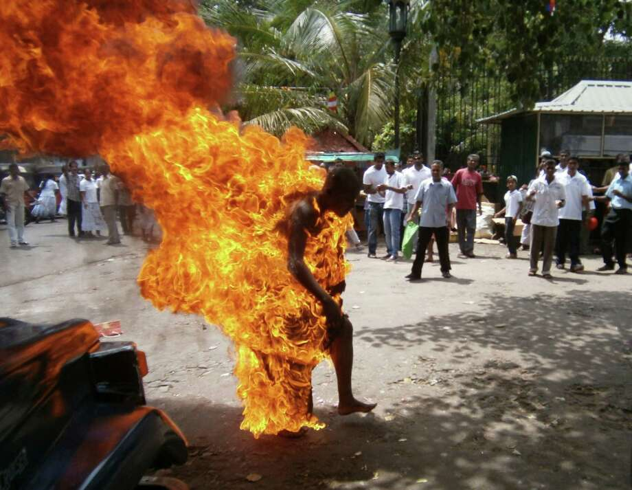 A Sri Lankan Buddhist monk identified as Bowatte Indrarathane walks after self immolating outside the sacred Temple of the Tooth in Kandy, Sri Lanka, Friday, May 24, 2013.  Sri Lankan police said the Buddhist monk has suffered serious injuries after setting himself on fire to protest the slaughter of cattle.  He reportedly had told other monks that he was burning himself to protest the killing of cattle for meat. Photo: AP