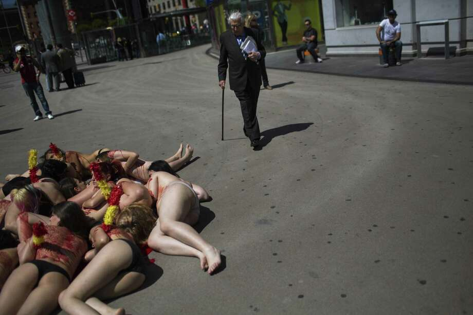 A man walks past partially clothed anti-bullfighting women activists covered with fake blood as they pose for photographs, during an event condemning bullfighting in the country, in Barcelona, Spain, Thursday, May 23, 2013. Photo: AP