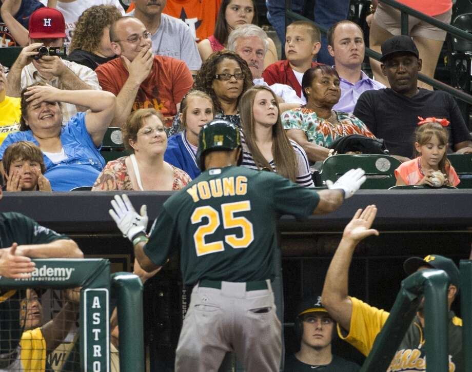 Astros fans react as Oakland's Chris Young celebrates after hitting a three-run home run during the ninth inning.