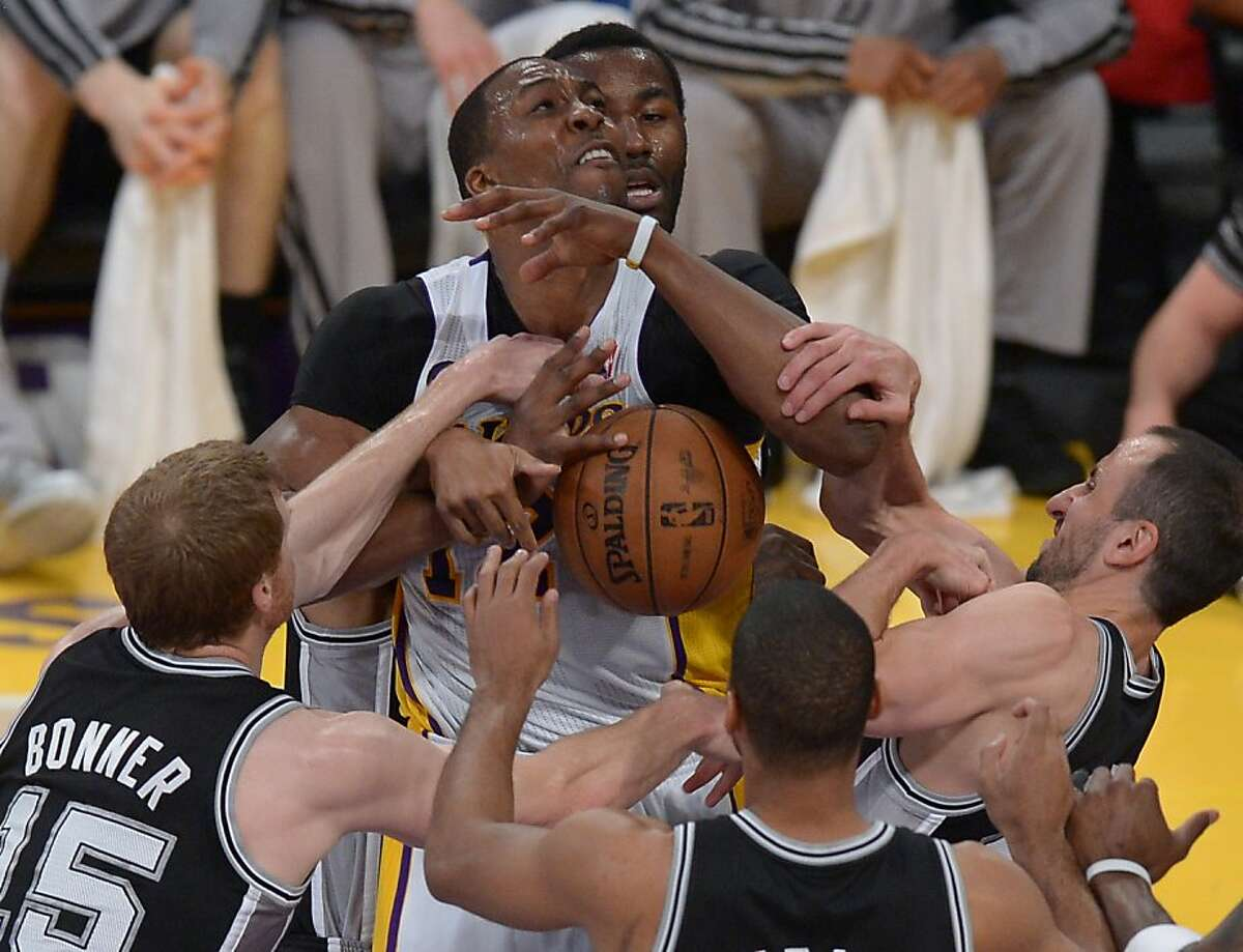 Dwight Howard (top) of the Los Angeles Lakers plays against the San Antonio Spurs players during Game Four of the NBA Western Conference Quarterfinal Playoffs at Staples Center in Los Angeles, California on April 28, 2013. AFP PHOTO / JOE KLAMARJOE KLAMAR/AFP/Getty Images