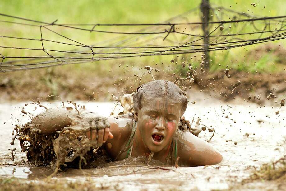 Eliza Rushton, 15, of Baker City, Ore., splashes through a mud pit during The Original Mud Run at Sam Houston Race Park Saturday, May 25, 2013, in Houston. Participants raced through 5K and 10K courses, over, under and through more than 20 muddy obstacles to benefit feedOne. Photo: Brett Coomer, Houston Chronicle / © 2013 Houston Chronicle