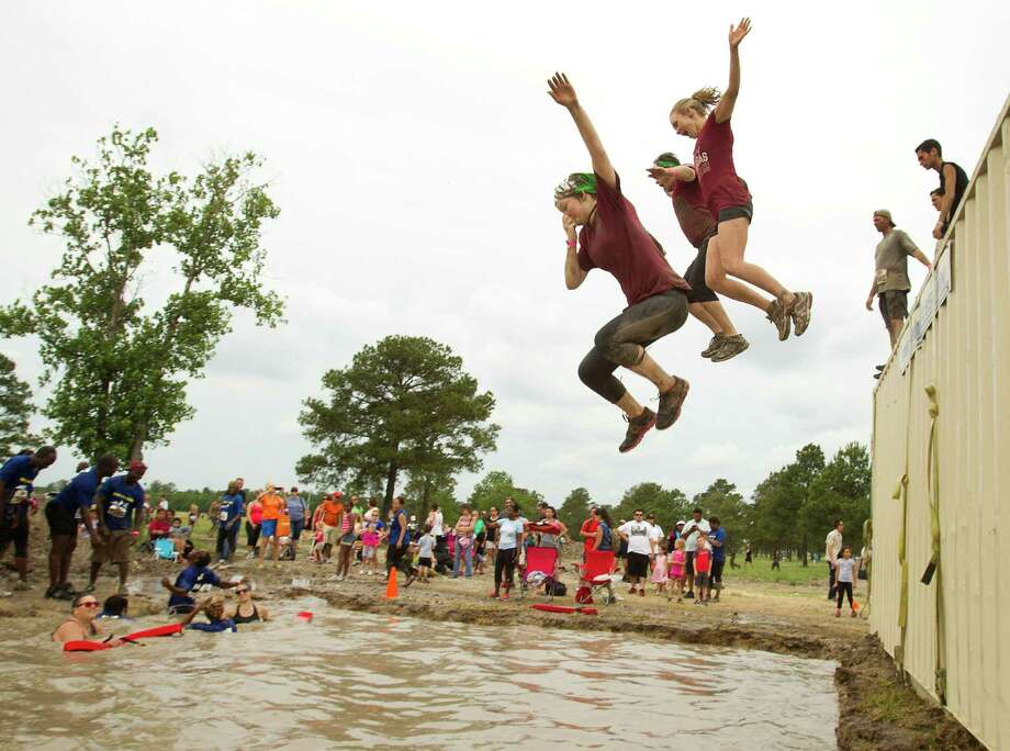 Racers leap into a mud pit during The Original Mud Run at Sam Houston Race Park Saturday, May 25, 2013, in Houston. Participants raced through 5K and 10K courses, over, under and through more than 20 muddy obstacles to benefit feedOne. Photo: Brett Coomer, Houston Chronicle / © 2013 Houston Chronicle