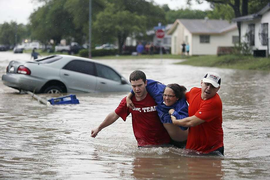 Marco Fairchild (left) and Gary Garza help Sueann Schaller from her car after she drove it into floodwaters in San Antonio's Westwood Village neighborhood. Photo: Lisa Krantz, Associated Press