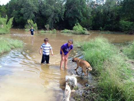 Children play in the flooded trail at Stone Oak Park on Saturday afternoon. Photo: Abe Levy / San Antonio Express-News