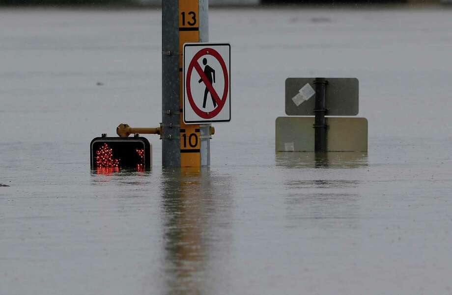 A flood gage shows waters just under 10 feet at an intersection, Saturday, May 25, 2013, in San Antonio. (AP Photo/Eric Gay) Photo: Eric Gay