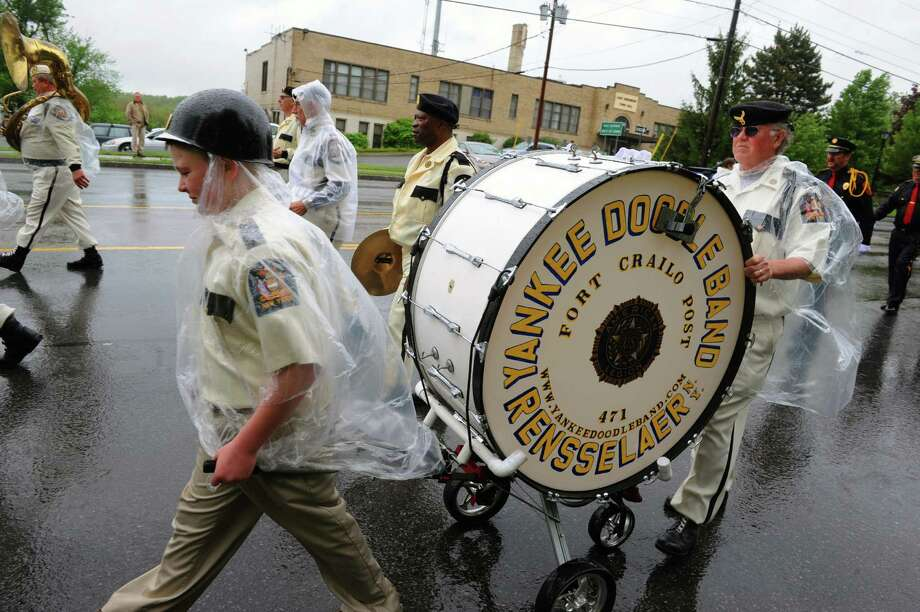 Clad in rain gear, with instruments at ease, the Yankee Doodle Band of Rensselaer marches in the annual East Greenbush Memorial Day Parade on Saturday May 25, 2013 in East Greenbush, N.Y. (Michael P. Farrell/Times Union) Photo: Michael P. Farrell