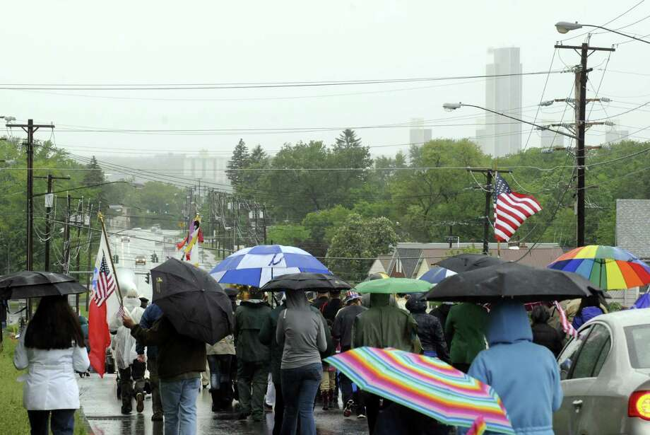 An umbella carrying crowd marches in the annual East Greenbush Memorial Day Parade on Saturday May 25, 2013 in East Greenbush, N.Y. (Michael P. Farrell/Times Union) Photo: Michael P. Farrell