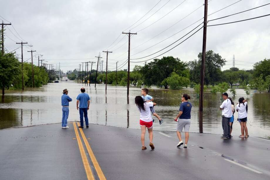 People gather on McCullough Avenue to view the floodwaters at Olmos Basin Golf Course after heavy rains hit the city on Saturday, May 25, 2013. Photo: Picasa, Glenda Wolin / For The San Antonio Express-News