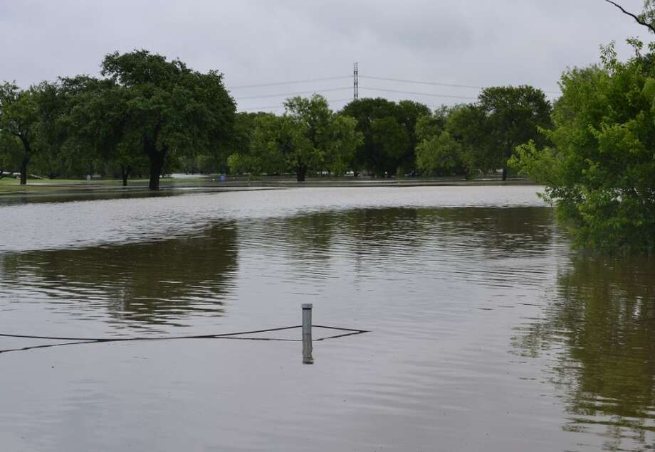 A fence at Olmos Basin Golf Course is seen under water after heavy rains hit the city on Saturday, May 25, 2013. Photo: Picasa, Glenda Wolin / For The San Antonio Express-News