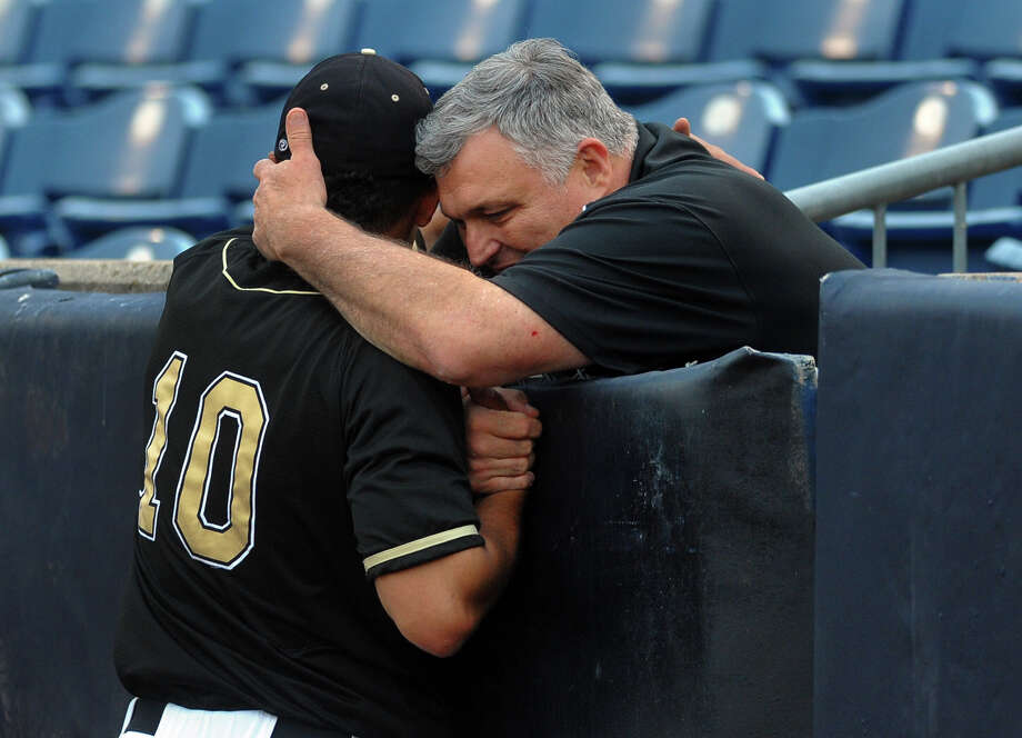 Trumbull High's Athletic Director, Mike Herbst, hugs Casey Mack after the team beat Greenwich, during FCIAC Baseball Championship semi-final action at the Ballpark at Harbor Yard in Bridgeport, Conn. on Wednesday May 22, 2013. Photo: Christian Abraham / Connecticut Post