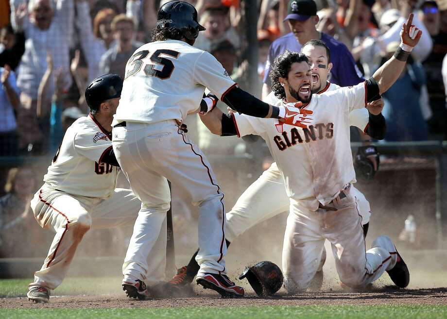 Marco Scutaro (left), Brandon Crawford and Andres Torres greet Angel Pagan after he slid home with the winning run. Photo: Michael Macor, The Chronicle