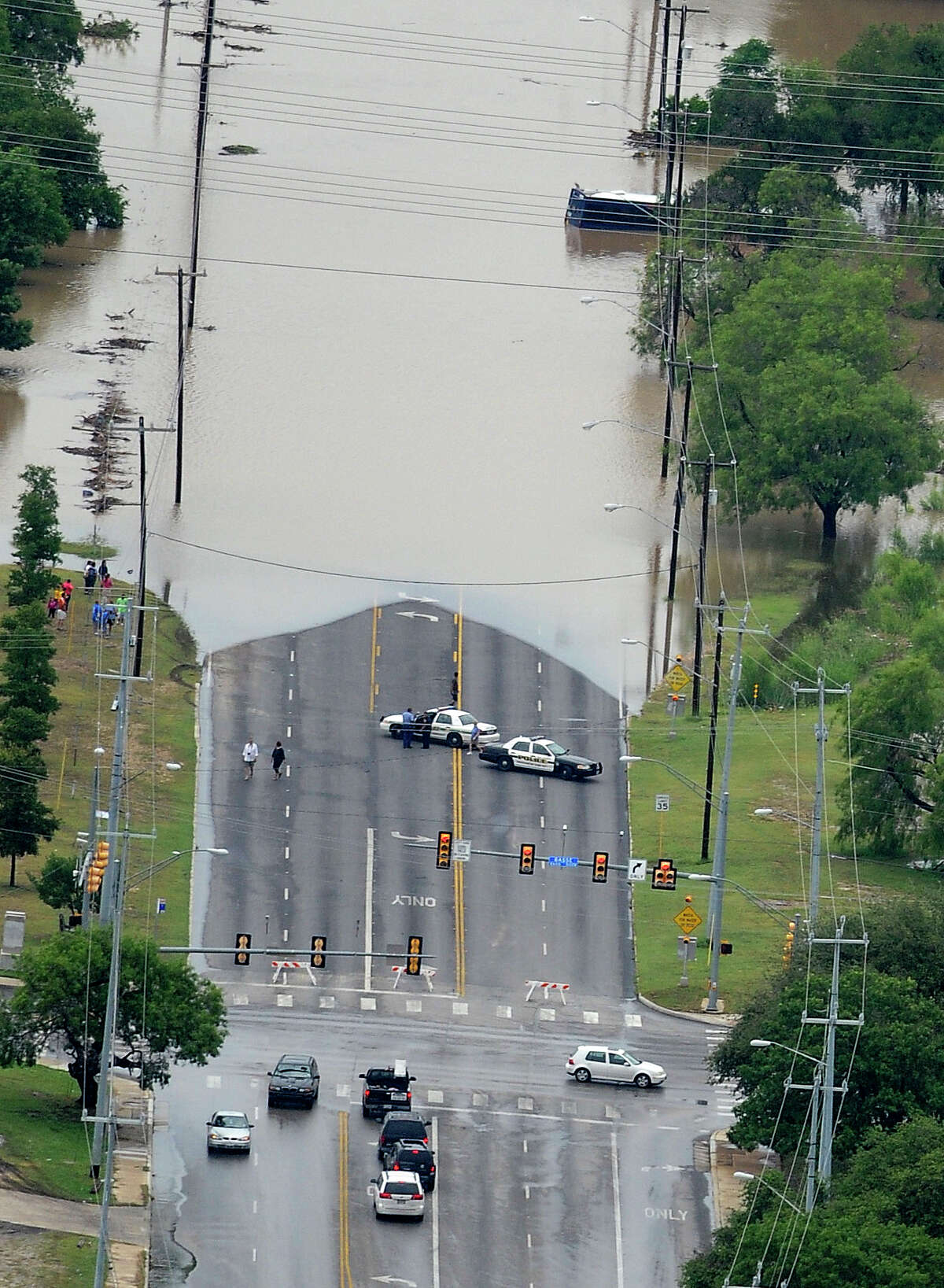 Police block a flooded portion of McCullough north of Basse where a bus is stranded in the water after heavy rains in San Antonio on Saturday morning, May 25, 2013.