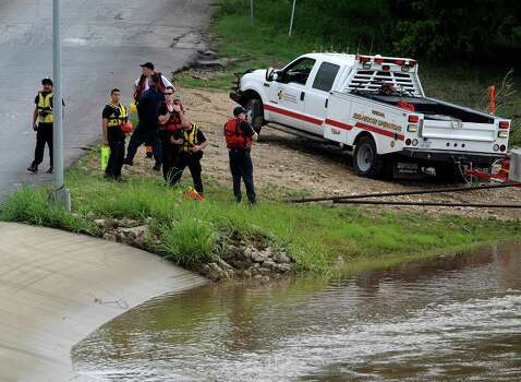 Rescuers in search search for a boy who was swept away by rushing water after heavy rains on Saturday, May 25, 2013. Photo: Billy Calzada, San Antonio Express-News / San Antonio Express-News