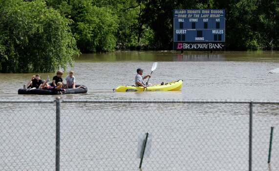 A kayaker pulls a raft with children around a flooded baseball park in San Antonio, Saturday, May 25, 2013, in San Antonio. San Antonio International Airport recorded more than nine inches of rain since midnight. (AP Photo/Eric Gay) Photo: Eric Gay, Associated Press / AP