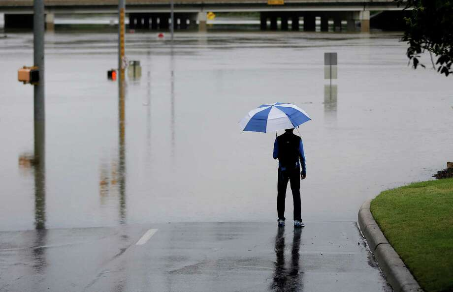 A man surveys floodwaters caused by heavy rains, Saturday, May 25, 2013, in San Antonio. The city has received torrential rains since Friday evening and officials say numerous roads have been closed because of flash flooding. (AP Photo/Eric Gay) Photo: Eric Gay, Associated Press / AP
