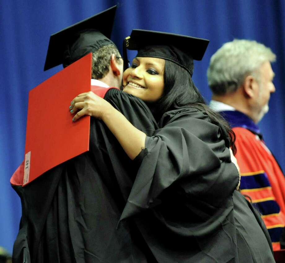 Graduate Tazy Montaz, center, receives her diploma and an embrace during RPI college commencement on Saturday, May 25, 2013, at Rensselaer Polytechnic Institute in Troy, N.Y. (Cindy Schultz / Times Union) Photo: Cindy Schultz / 10022129A