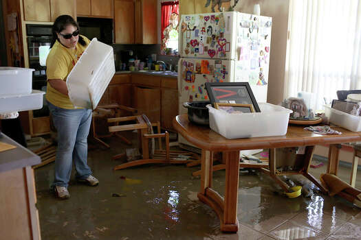 Anthony Wilfong carries Celia Olivarez's wedding portrait out of her home which was flooded with several feet of water on Espada Rd. on Saturday, May 25, 2013. The photo was taken at nearby Mission Espada and was undamaged by the flood. Photo: Express-News File Photo, San Antonio Express-News / San Antonio Express-News