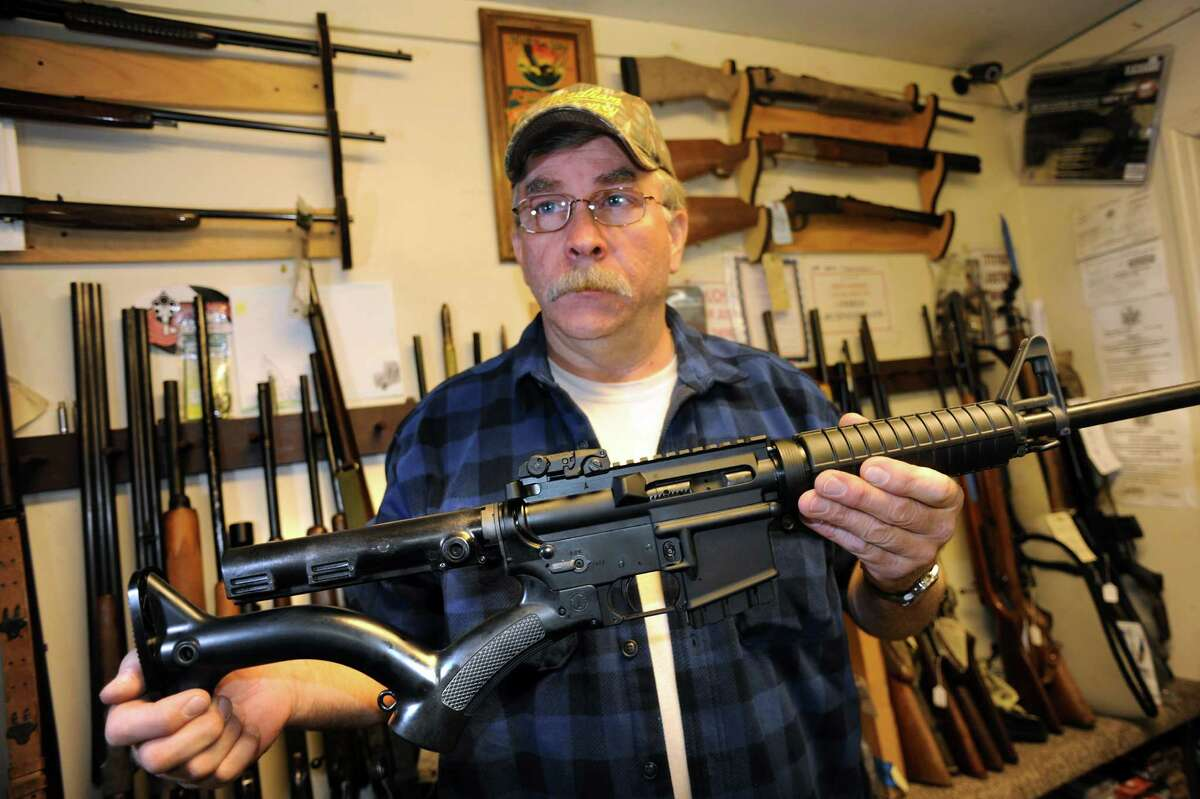 Shop owner Rich Sehlmeyer holds an AR-15 assault-style rifle with a compliant stock on Saturday, May 25, 2013, at The Gun Shop in Lake Luzerne, N.Y. (Cindy Schultz / Times Union)