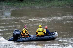 A water rescue team searches for a child that was swept away in Cibolo Creek in Schertz on the afternoon of Saturday, May 25, 2013. A police spokesman said that two young people attempted to cross the creek on foot, and one was swept away by the rushing waters.