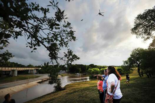 People watch from the banks of Cibolo Creek as a Texas Department of Public Safety helicopter joins in the search for a missing young person who was swept away by rushing water on Saturday at about 4:30 p.m. Photo: Billy Calzada, San Antonio Express-News / San Antonio Express-News