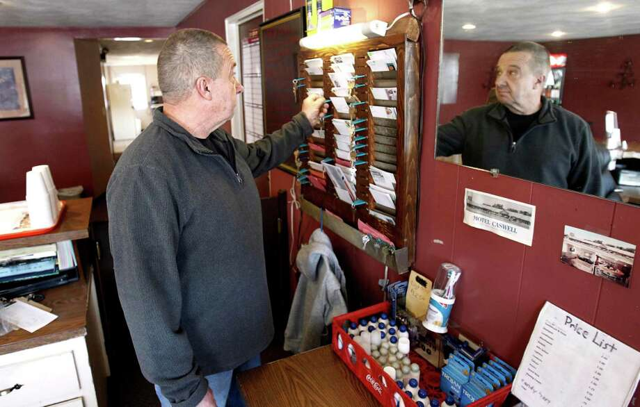 In this Wednesday, Nov. 9, 2011 photo, owner Russ Caswell reaches for a room key behind the front desk of the Motel Caswell in Tewksbury, Mass. Caswell is fighting to keep the federal government from taking his motel under a law that allows for forfeiture of properties connected to crimes. The government does not claim that Caswell committed any crimes, but claims there is drug-dealing among the motel's guests.  (AP Photo/Winslow Townson) Photo: Winslow Townson