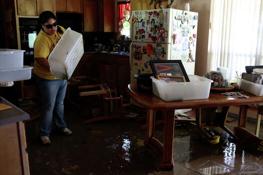 Valerie Wilfong cleans out flooded containers to pack with undamaged items at her aunt's home, which was flooded with several feet of water, on Espada Rd. on Saturday, May 25, 2013. 54 people were rescued from the neighborhood. Photo: Lisa Krantz, San Antonio Express-News / San Antonio Express-News