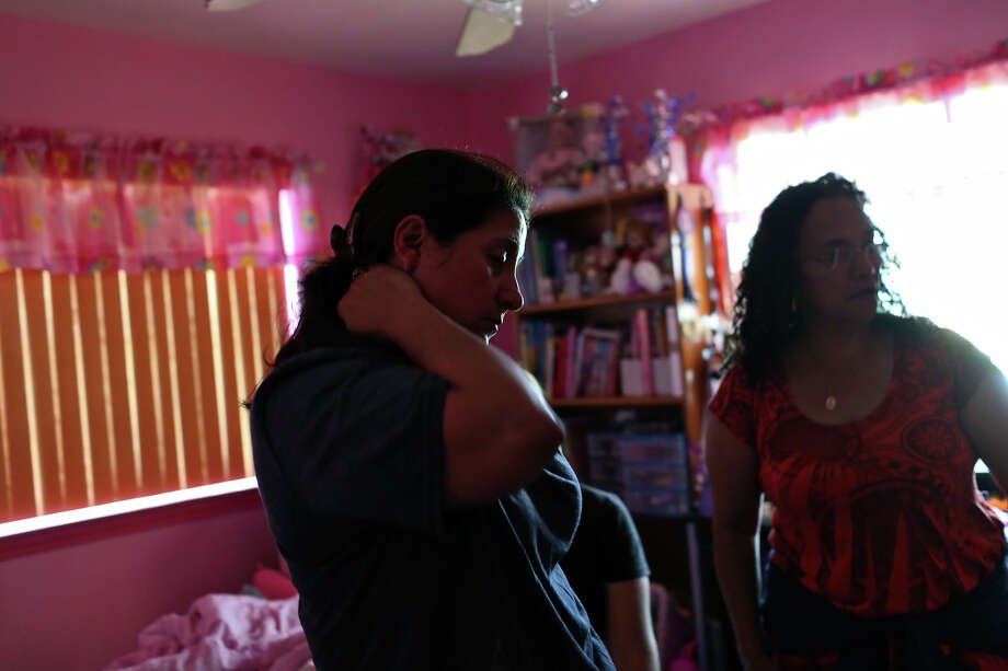 Celia Olivarez sees the damage to her seven-year-old daughter's room which was flooded with several feet of water on Espada Rd. on Saturday, May 25, 2013. Helping salvage items is Sylvia Cantu, right. Photo: Lisa Krantz, San Antonio Express-News / San Antonio Express-News