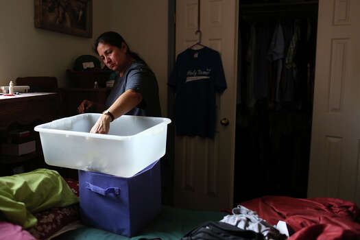 Celia Olivarez packs up items which were not flooded at her home which suffered damage from several feet of floodwater on Espada Rd. on Saturday, May 25, 2013. 54 people were rescued from the neighborhood. Photo: Lisa Krantz, San Antonio Express-News / San Antonio Express-News