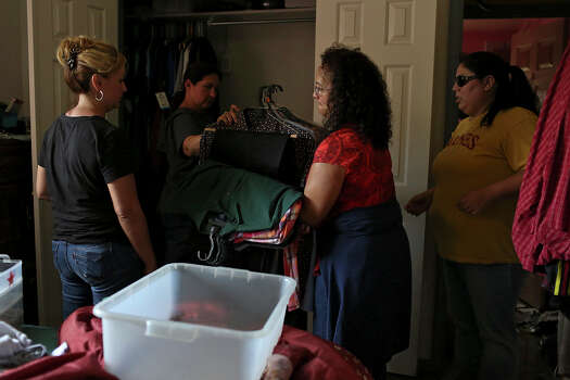 Celia Olivarez, center,/left, with the help of her niece, from left, Veronica Martinez, Sylvia Cantu and niece Valerie Wilfong, packs up items which were not flooded at her home which suffered damage from several feet of floodwater on Espada Rd. on Saturday, May 25, 2013. 54 people were rescued from the neighborhood. Photo: Lisa Krantz, San Antonio Express-News / San Antonio Express-News