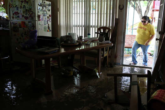 Valerie Wilfong helps salvage undamaged items at her aunt's home, which was flooded with several feet of water, on Espada Rd. on Saturday, May 25, 2013. 54 people were rescued from the neighborhood. Photo: Lisa Krantz, San Antonio Express-News / San Antonio Express-News