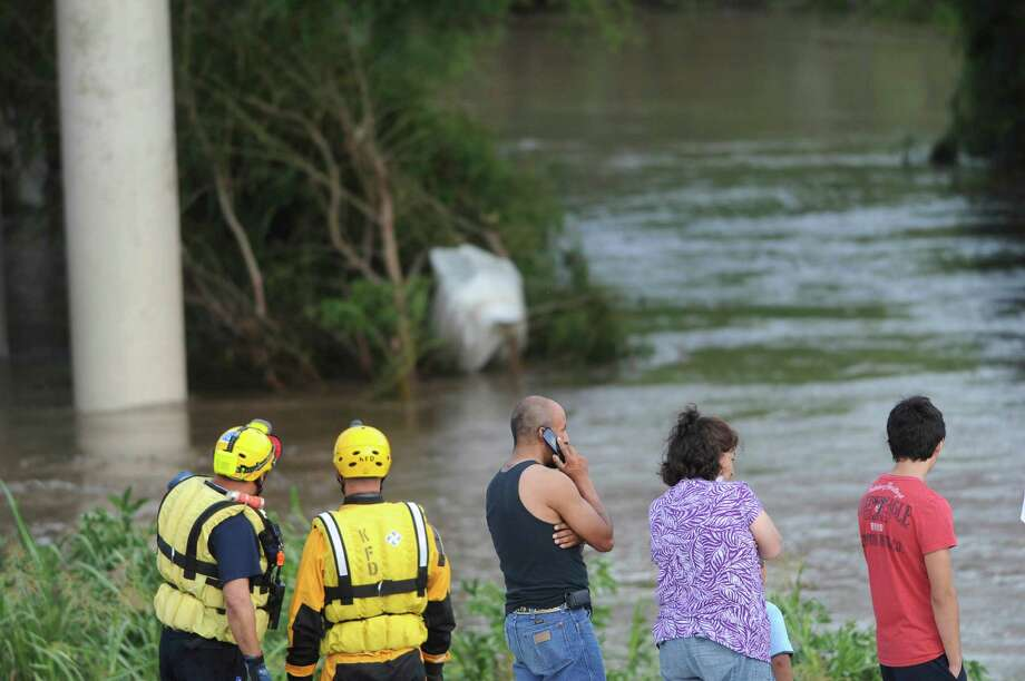 Water rescuers and others watch for a young person who was swept away by the rushing waters of Cibolo Creek on Saturday afternoon, May 25, 2013. A police spokesman said that two young people attempted to walk or swim across the creek, and one was swept away. Photo: Billy Calzada, San Antonio Express-News / San Antonio Express-News