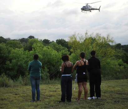 People watch as a Texas Department of Public Safety helicopter searches Cibolo Creek for a missing young person who was swept away by rushing waters on Saturday afternoon, May 25, 2013. Photo: Billy Calzada, San Antonio Express-News / San Antonio Express-News